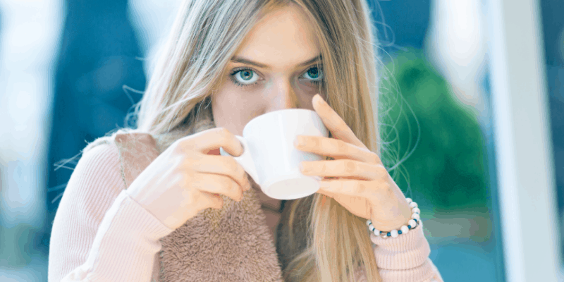 Girl drinking from a coffee cup for my article on Does Taking a Break Mean You're Single (Fully Answered)