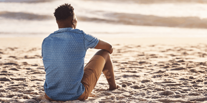 Man sitting on the beach with his back to the camera—how to ask for a second chance in a relationship