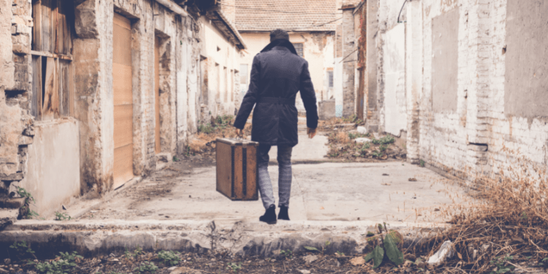 Man with a suitcase walking through an alley—for my article ,Is Dating Harder For Men (Solved)
