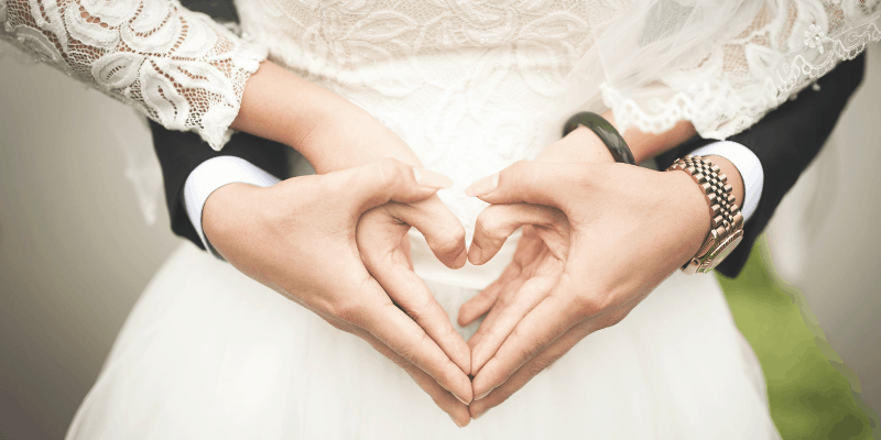 Bride and Groom making hearts with their hands—the sanctity of marriage