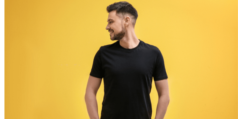 A man in a black shirt against a yellow background—What Color Should a Man Wear on a First Date