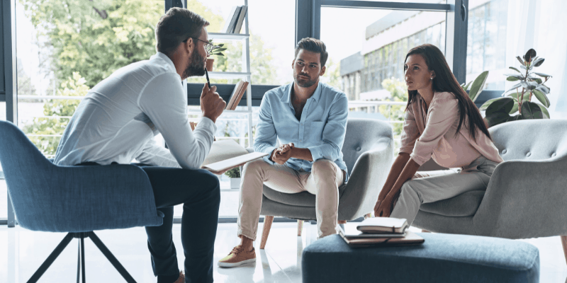 Two men and a woman sitting and talking—for my article on Who is the best relationship coach (Solved)