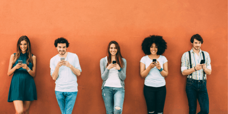 Five men and women against a wall texting—Do You Keep Texting After a Scheduled Date