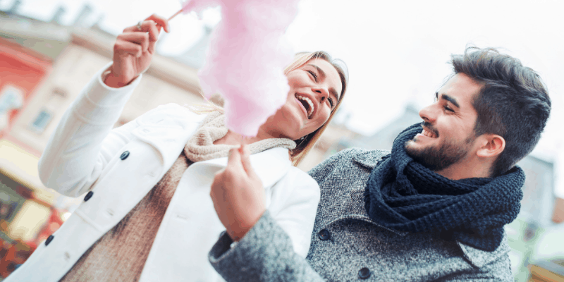 A man a woman smiling and eating cotton candy—Is Dating For 10 Years Too Long (Fully Answered)