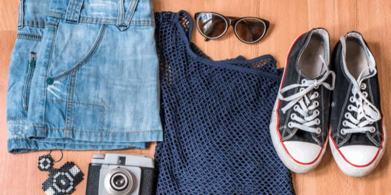 Jean shorts, cool top, sunglasses and a camera laid out on the floor