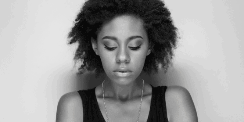 Black woman looking down and sad—how to break up with a Gemini guy