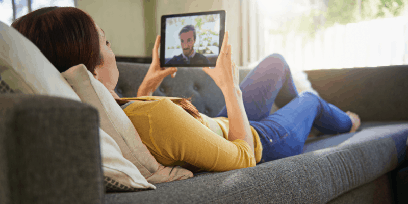 Woman laying on couch talking to man by video chat on tablet—What is Considered a Long Distance Relationship